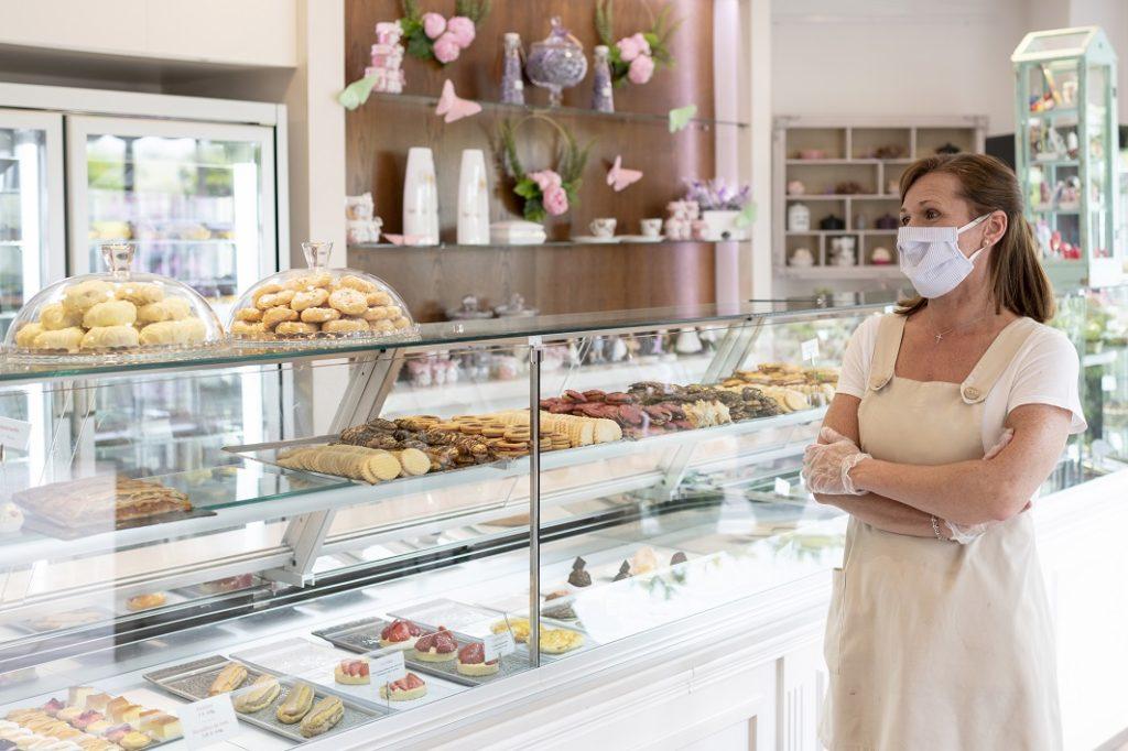 Ladenbesitzerin mit Schutzvorkehrungen gegen Corona